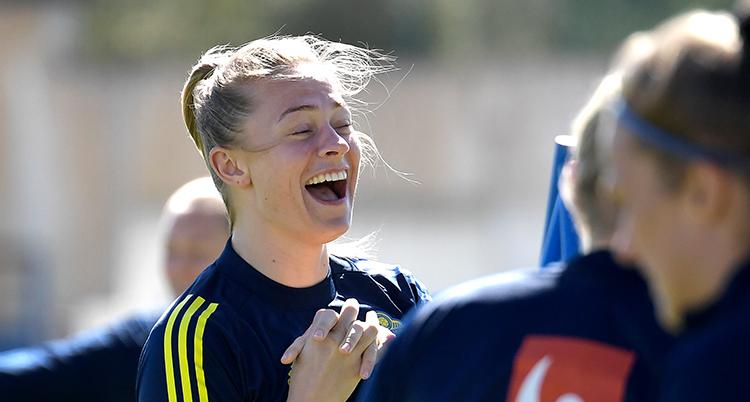 Rolfö skrattar och blundar. Hon har träningskläder på sig och stor med några andra spelare.