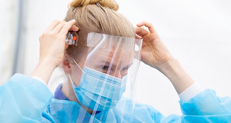 En kvinna sätter på sid ett visir. Hon har blå kläder och munskydd