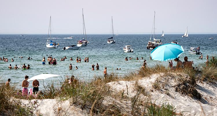 En sandstrand med människor och flera parasoller.