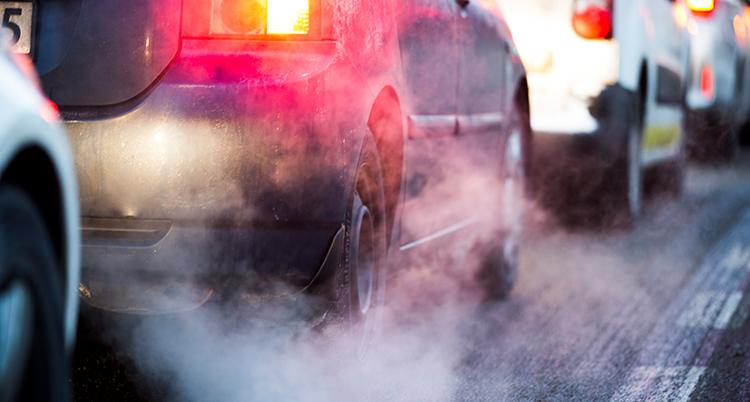 Närbild på bilar bakifrån. De står i kö och det kommer rök och avser från dem.