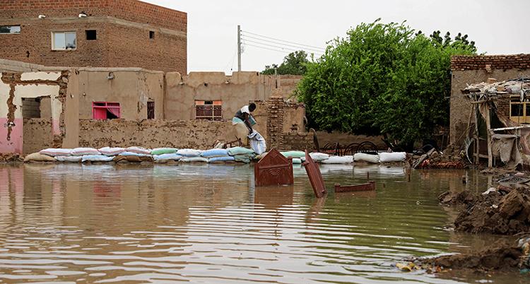 marken framför ett hus är helt fylld av vatten. En man fyller sandsäckar för att försöka stoppa vattnet.