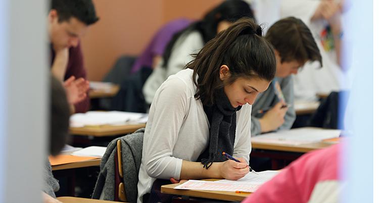 Bilden visar ett rum. Där sitter personer vid varsin bänk. De ser koncentrerade ut. De skriver med pennor på papper.
