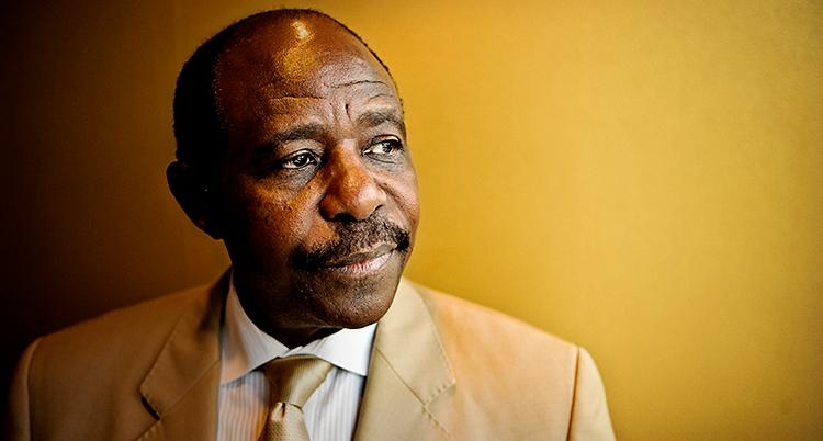 Han står framför en gul vägg. Han tittar åt sidan. Han har lite skägg och kostym och slips. Han är mellan 60 och 70 år.