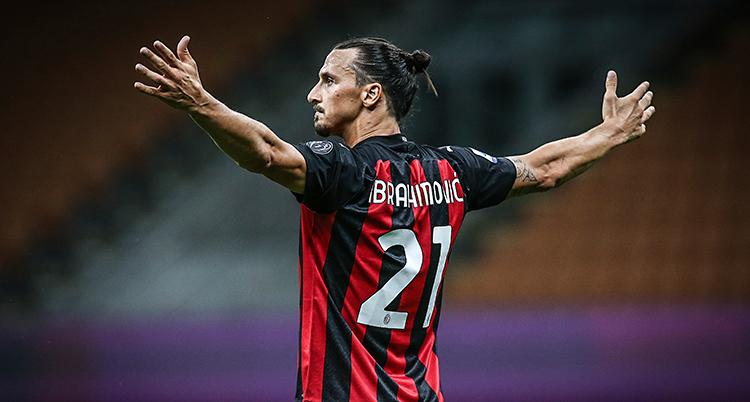 Bilden är från en match i fotboll. Zlatan firar ett mål. Han sträcker ut armarna. Han har håret i en tofs. Hans tröja är randig i svart och rött.