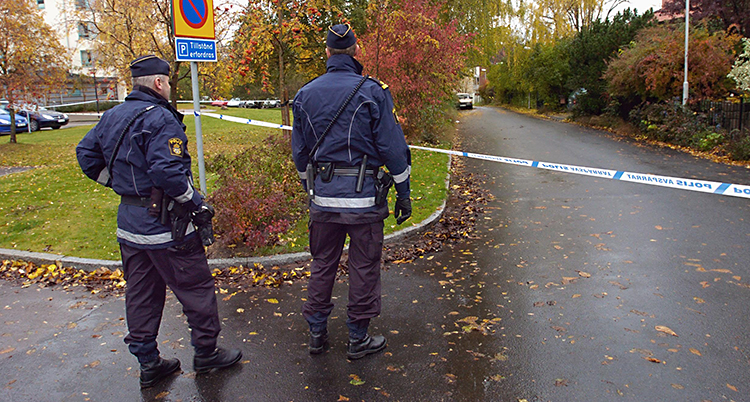 Bilden är tagen utomhus. Det är höst och regnigt. Två poliser står på en gata. De har ryggen mot kameran. Poliserna har spärrat av gatan med blå och vita band.