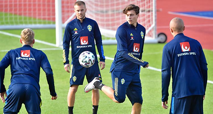 Fyra män är på en fotbollsplan. En av dem klackar bollen. De har på sig blå dräkter.