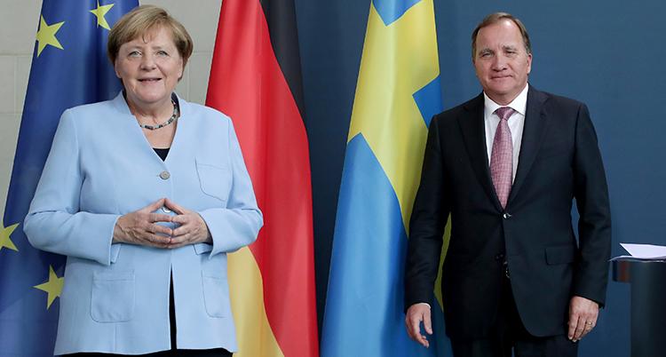 ANgela Merkel och Löfven framför EUs Tysklands och Sveriges flaggor. De ser glada ut.