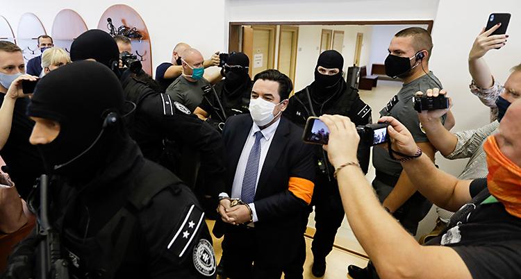 En man är i en domstol. Han går genom ett rum. Han har kostym, munskydd och handbojor. Poliser med masker och stora gevär följer honom. Runt om finns journalister som filmar och tar bilder.