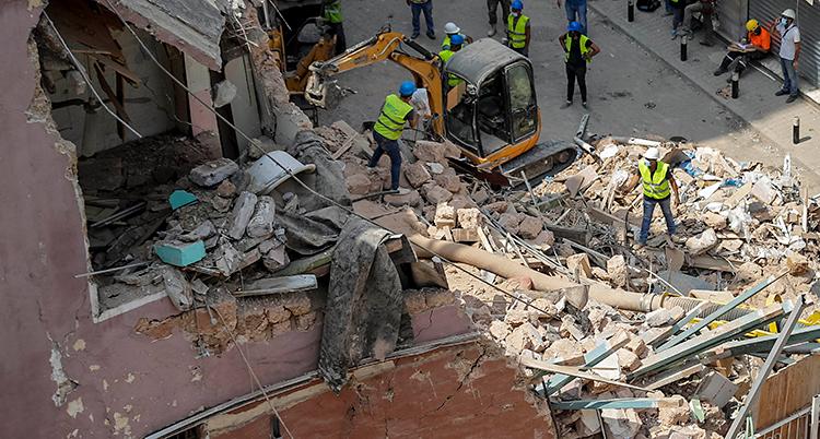 Ett hus är alldeles förstört. Arbetare med hjälmar letar i bråten. De har också hjälp av en liten grävmaskin.