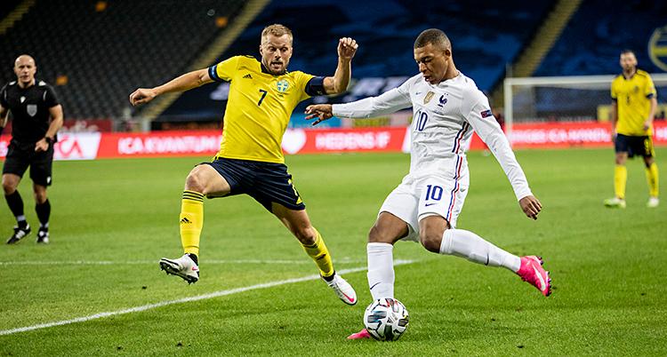 Vi ser en match i fotboll. En fransk spelare har bollen. En svensk spelare försöker ta bollen.