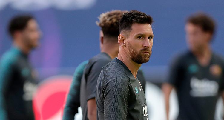 Lionel Messi är på en fotbollsplan. Det är träning. Han har en grå tröja på sig. På sin högra arm har han tatueringar.