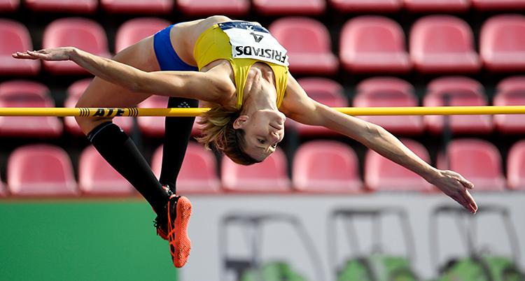 Sofie Skoog hoppar över ribban. Hon ligger i luften. Hon har ett gult linne och korta blå byxor.