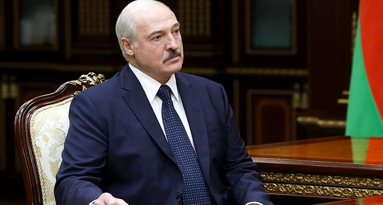 Lukasjenko i blå kostym i en vackert snidad stol på sitt kontor.