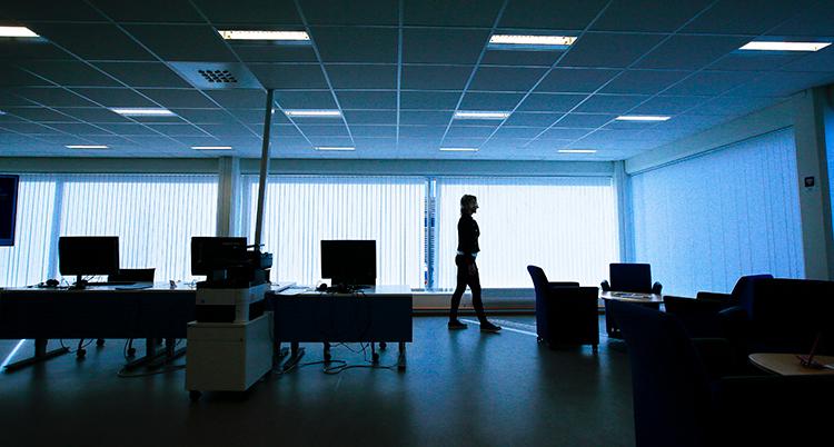 En silhuett av en person i ett mörkt kontorslandskap