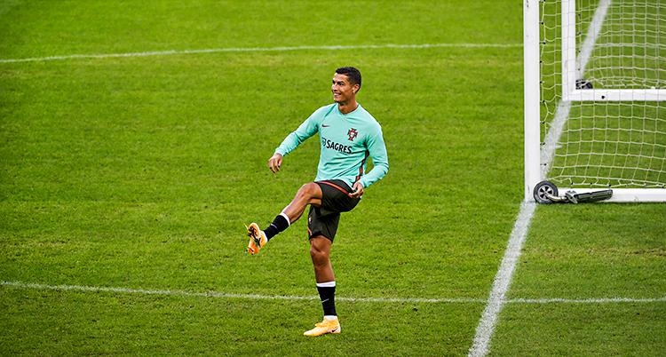Cristiano Ronaldo är på en fotbollsplan. Han har precis sparkat iväg en boll. Han ler och är glad.