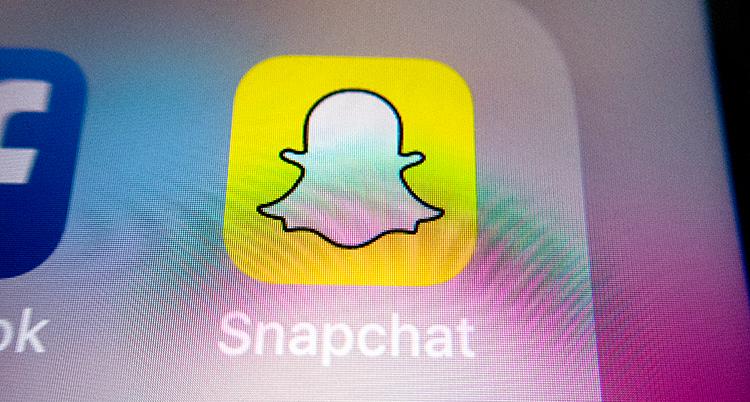 Vi ser skärmen på en mobiltelefon. Där är symbolen för Snapchat. Det är en vitt spöke på en gul bakgrund.