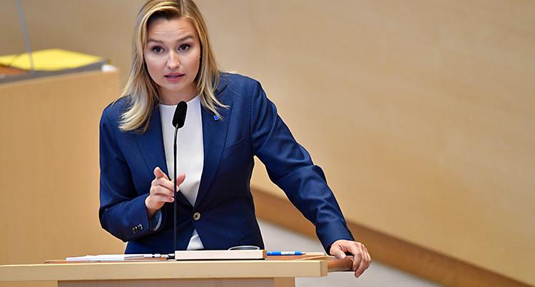 Ebba Busch står i talarstolen i riksdagen. Hon pratar i en mikrofon. Hon har vit tröja och blå kavaj.