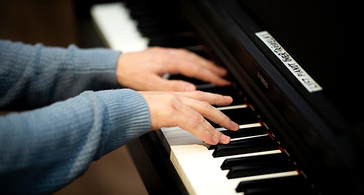 Vi ser armarna på en person som spelar piano. Personen har en grå tröja. Tangenterna på pianot är vita och svarta.