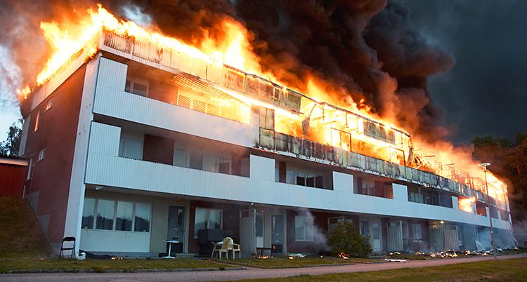 Vi ser ett stort hus med lägenheter. Huset är fyra våningar. I toppen av huset brinner det kraftigt. Det kommer mörk rök från elden.