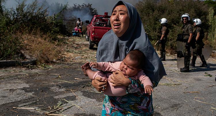 En kvinna i förgrunden ser rädd ut. Hon har ett litet barn i famnen. I bakgrunden ser vi poliser. Det ryker bakom en bil som om det brinner.