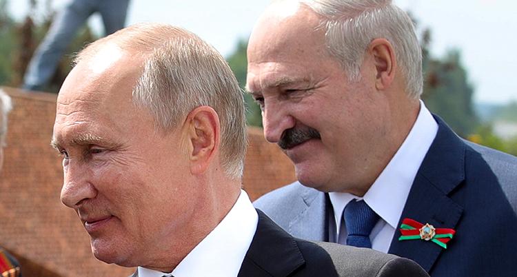 Putin och Lukasjenko står nära varandra, båda i profil, vända åt samma håll. De ler. Bilden visar bara männens huvuden.