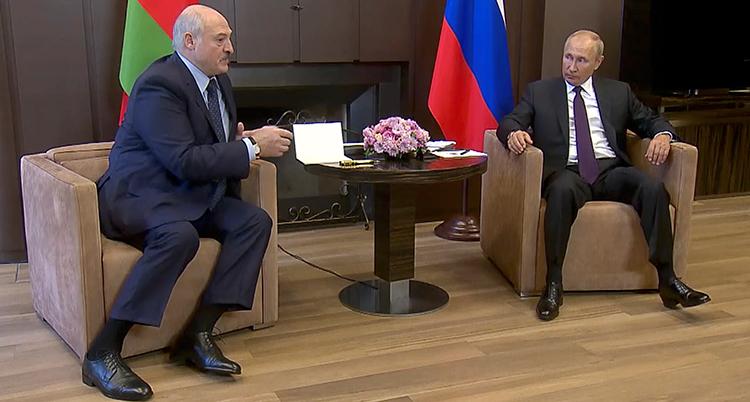 Lukasjenko sitter i en fåtölj vid ett litet bord. På andra sidan bordet sitter Putin.