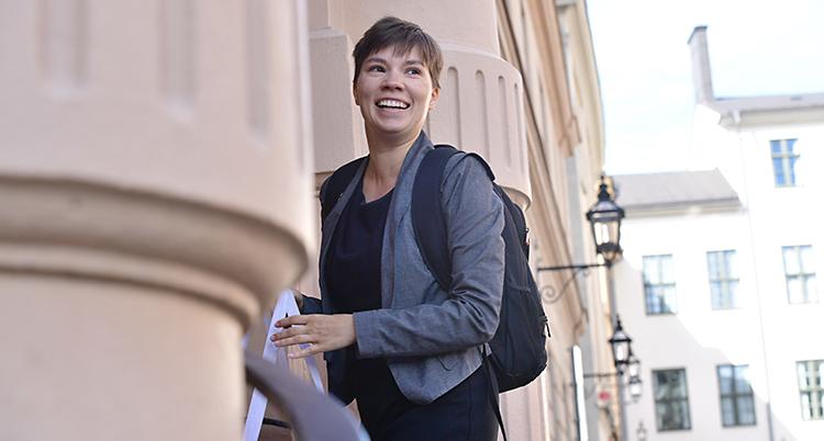 Hon är på väg uppför en trappa. Hon vänder sig lite om, och ler. Hon har kort hår. Hon har en grå kavaj och en svart ryggsäck.
