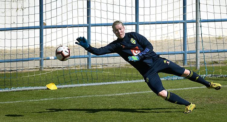 Hedvig Lindahl på en träning. Hon står i mål. Hon kastar sig mot en boll som kommer.
