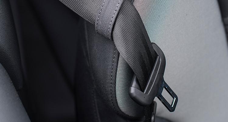Bilden är tagen inuti en bil. Vi ser ett säte. Ovanpå säte följer ett bälte. Bältet är svart. Längst ut på bältet finns en del av plast och en del av metall.