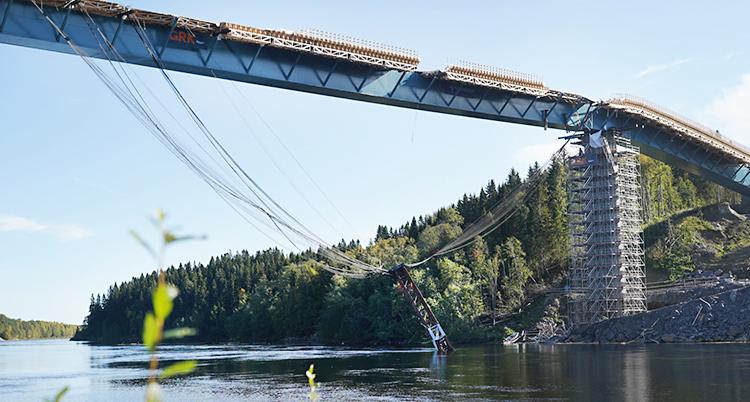 Bilden är tagen utomhus. Vi ser en bro som håller på att byggas över vatten. En stor bit av metall hänger ner från bron i vajrar. Den hänger nere vid vattnet.