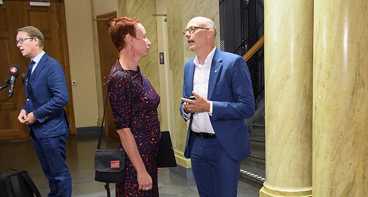 Tre personer står i en sal. En man blir intervjuad av en journalist. En kvinna och en man står och pratar med varandra.