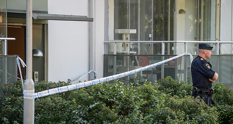 Vi ser ett hus med lägenheter. Poliserna har spärrat av med band som är blå och vita. En polis står och vaktar.