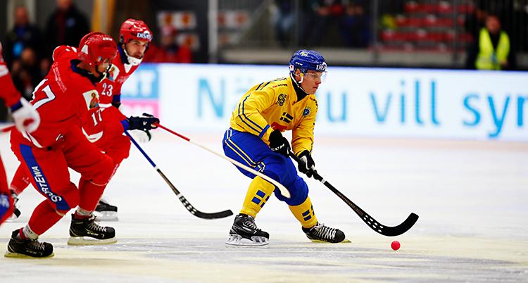 Från en match i bandy. En spelare i Sverige har bollen. Spelare från Ryssland jagar honom.