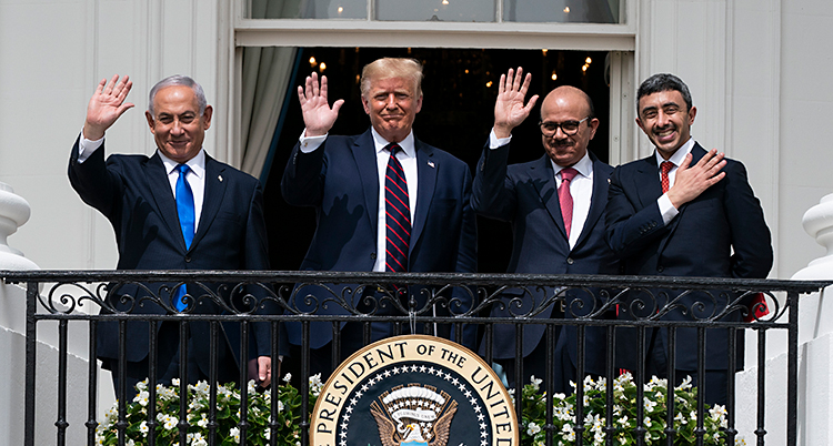 Fyra män står på en balkong och vinkar. På balkongen finns ett märke där det står United States of America.