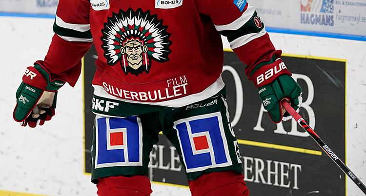 En ishockeyspelare på isen. Han har en röd tröja. På tröjan finns en person från urbefolkningen i Amerika, med fjädrar på huvudet.