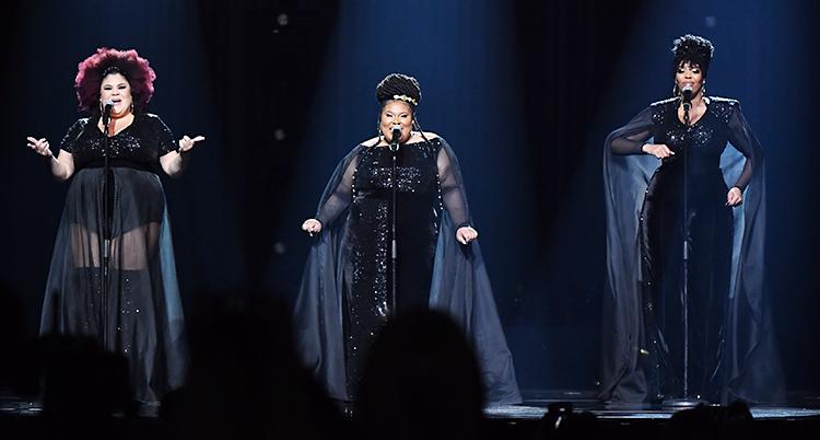 Tre kvinnor står på en scen. De sjunger i varsin mikrofon. De har mörka kläder.