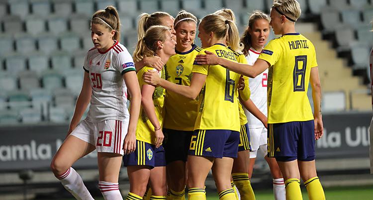 Flera spelare står i en grupp och kramar om varandra. En av dem har gjort mål i fotboll. De har gula t-shirts och blå shorts.
