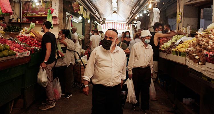 Bilden är från en marknad. Människor går runt och köper grönsaker och annan mat.