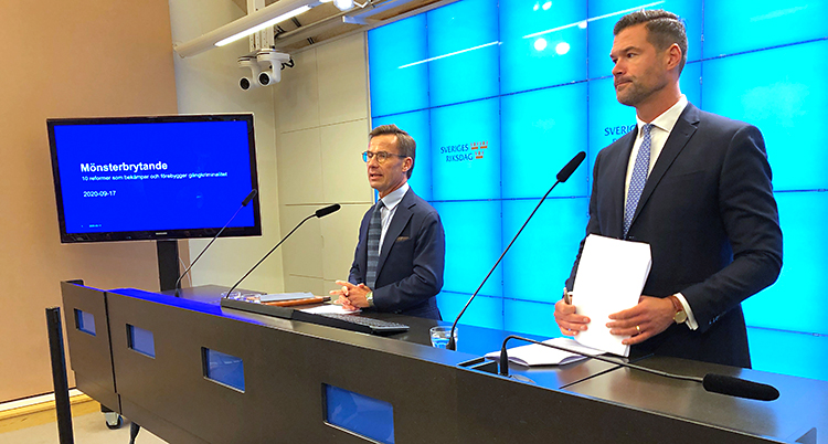 Två män står vid en bänk. De pratar i varsin mikrofon. Båda männen har kostym och slips. Mannen till vänster har glasögon. Bakom dem på väggen står det Sveriges riksdag.