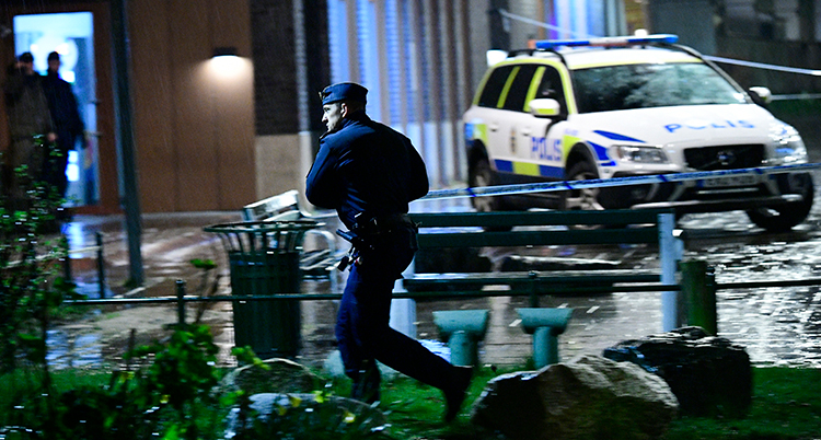 en polis springer framför en polisbil.