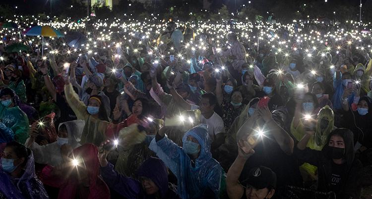 massor av människor står på ett torg och håller upp sina telefoner med lamporna lysande. Det är kväll.