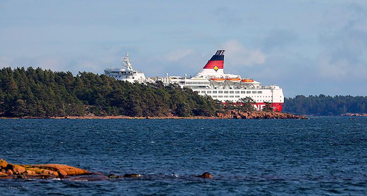 Vi ser ett hav och några öar. Bakom en av öarna syns en stor båt. Den är vit och har lite rött på sig.