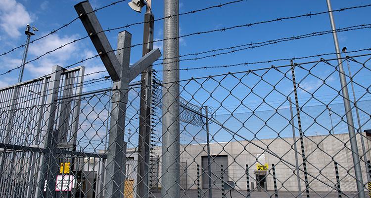 Ett staket utanför ett fängelse med taggtråd högst upp.