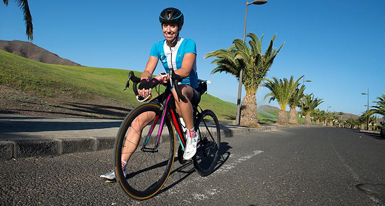 Lisa Nordén sitter på en cykel. Cykeln står stilla på en väg. Hon ler och tittar in i kameran. Hon har hjälm på sig. I bakgrunden syns palmer.