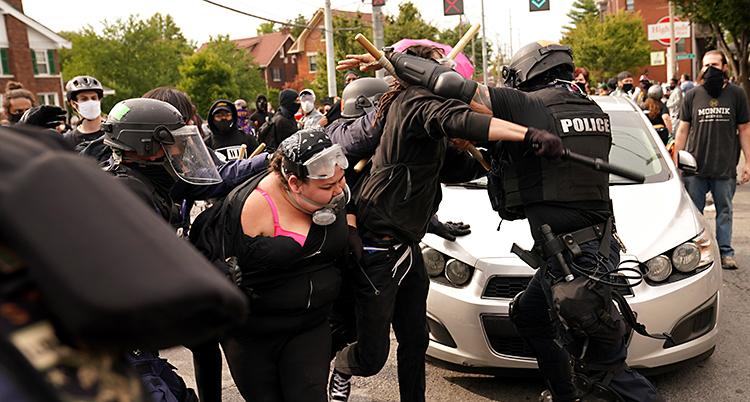 En man ser ut att brottas med en polis. Och en kvinna hålls fast av en annan polis. De är utomhus på en gata.