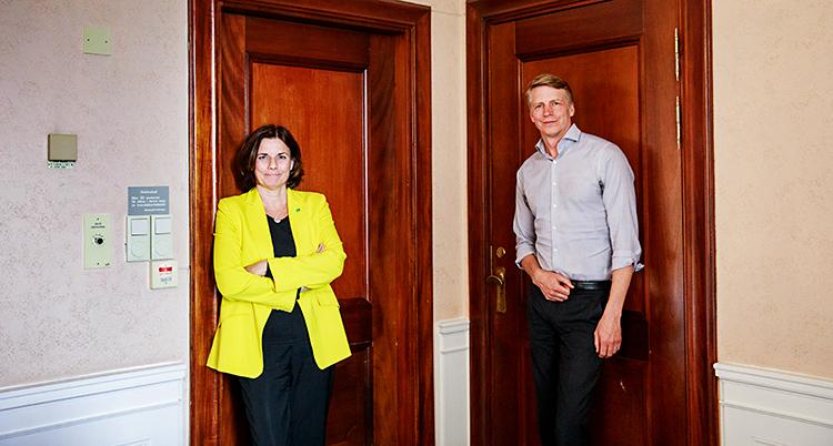 Bilden är tagen inomhus. De står mot varsin dörr. Lövin står till vänster. Hon har en gul kavaj. Bolund står till höger. Han har en grå skjorta.
