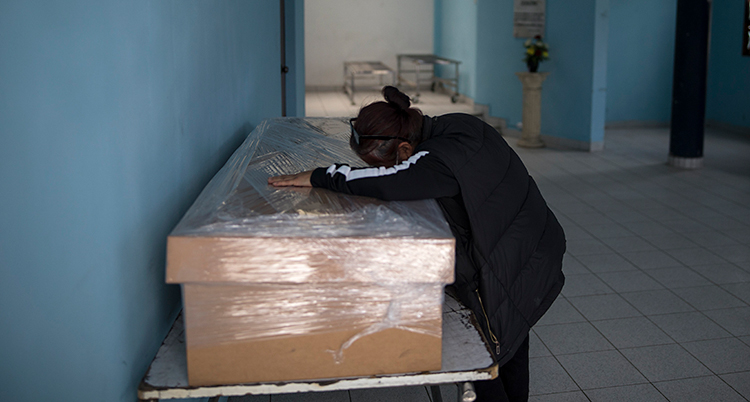 Vi ser ett rum med blå väggar. En kvinna lutar sig över en stor låda. Hon är ledsen. I lådan ligger kroppen från hennes döda man.