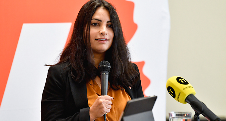 Hon står och pratar i en mikrofon. Hon har en svart kavaj och orange tröja. I bakgrunden är Vänsterpartiets symbol.