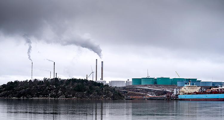 Bilden är tagen från vattnet. Vi ser en stor fabrik. Det kommer rök ur höga skorstenar. En stor båt finns vid fabriken.
