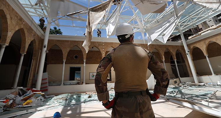 Vi ser ryggen på en soldat. Han har en vit hjälm. Han tittar ut över en skolgård. Det ligger krossat glas och skräp på marken. Och taket är helt trasigt.
